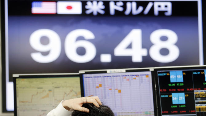 A currency trader checks monitors at a foreign exchange company in Tokyo, Friday, April 5, 2013. Japan's benchmark stock index surged above 13,000 for the first time in more than four years Friday, its second straight day of big gains after the central bank announced aggressive action to lift the economy out of a prolonged slump. The central bank's announcement dragged down the yen, giving a boost to shares of Japan's powerhouse manufacturers. (AP Photo/Koji Sasahara)