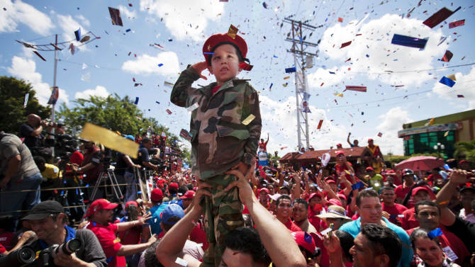 A boy dressed as a soldier salutes during a campaign caravan of Venezuela's President Hugo Chavez from Barinas to Caracas, in Sabaneta, Venezuela, Monday, Oct. 1, 2012. Venezuela's presidential election is scheduled for Oct. 7. (AP Photo/Rodrigo Abd)