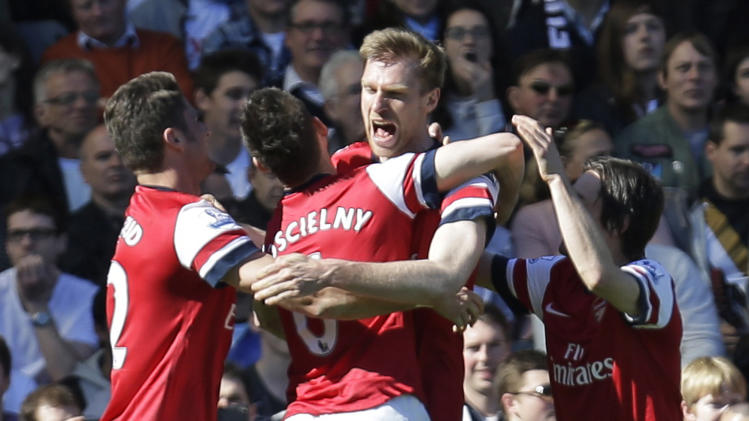 Arsenal players celebrate with their teammate Per Mertesacker, 2nd right, after he scored against Fulham during their English Premier League soccer match at the Craven Cottage ground in London, Saturday, April 20, 2013. Arsenal won the match 1-0.(AP Photo/Lefteris Pitarakis)