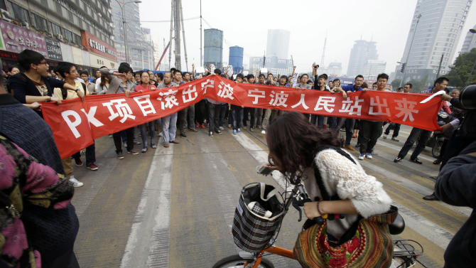 """Protesters march with a banner which reads """"Project PX get out of Ningbo, Ningbo people stand up""""  in Zhejiang province's Ningbo city, protesting the proposed expansion of a petrochemical factory Sunday, Oct. 28, 2012. Thousands of people in the eastern Chinese city clashed with police Saturday while protesting the proposed expansion of the factory that they say would spew pollution and damage public health, townspeople said. (AP Photo/Ng Han Guan)"""