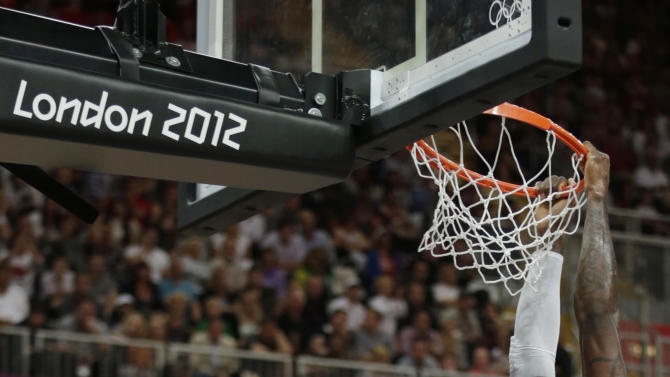 USA's Lebron James hangs on the rim following a dunk during the first half of a preliminary men's basketball game against France at the 2012 Summer Olympics, Sunday, July 29, 2012, in London. (AP Photo/Charles Krupa)