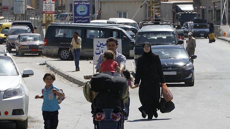 A family with their belongings after crossing Masnaa border post from Syria to Lebanon's Bekaa valley on August 31, 2013