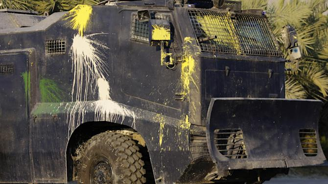 A police armored vehicle splattered with Bahraini anti-government protesters' paint bombs chases demonstrators in Sitra, Bahrain, on Friday, Feb. 12, 2016. Bahraini youths pelted armored vehicles and police jeeps with paint bombs, stones and petrol bombs after police moved in quickly with tear gas to quash an anti-government protest, one of several demonstrations held in the run-up to Sunday's 5th anniversary of Bahrain's Arab Spring uprising. (AP Photo/Hasan Jamali)