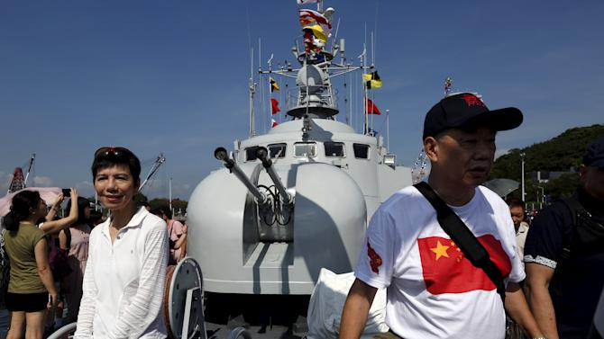 A visitor wearing a t-shirt featuring a Chinese national flag walks on a naval ship at a People's Liberation Army naval base in Hong Kong