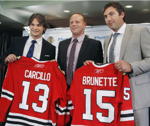 New Chicago Blackhawks free agent signees Daniel Carcillo and Andrew Brunette pose with general manager Stan Bowman, center, after being introduced at a news conference Monday, Aug. 8, 2011, in Chicago. (AP Photo/M. Spencer Green)