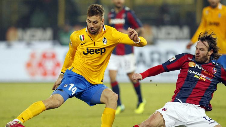 Juventus' Llorente is challenged by Bologna's Natali during their Italian Serie A soccer match at the Dall'Ara stadium in Bologna