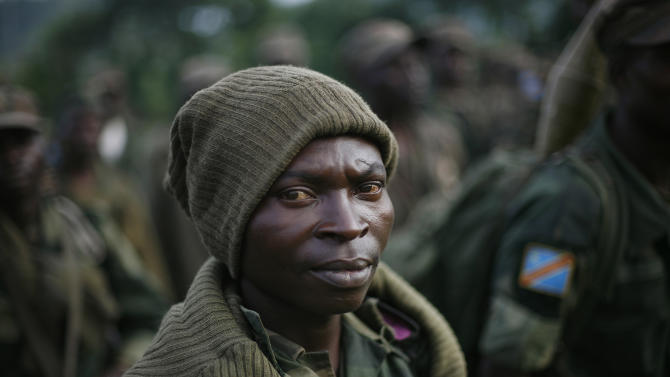 A member of the FARDC Congolese government special forces stands in a stadium  near Minova Congo some 40 kms south-west of Goma, Thursday Nov. 29, 2012, for a moral building gathering and an address by their commander General Bahouma .M23 Rebels, who last week seized one of the most important cities in eastern Congo and advanced beyond, said Thursday that they had pulled back several miles (kilometers ) to the town of Sake and were on track to leave the key city of Goma by Friday, in accordance with a deadline imposed by the international community. Government troops were massing in Minova.(AP Photo/Jerome Delay)