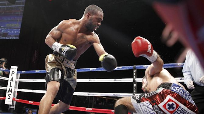 Gary Russell Jr., left, of the United States, knocks WBC featherweight champion Jhonny Gonzalez, of Mexico, to the canvas during their title fight in Las Vegas on Saturday, March 28, 2015. Russell took the title with a fourth-round win. (AP Photo/Las Vegas Sun/Steve Marcus)