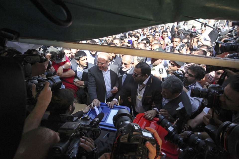 Tehran Mayor and Iranian presidential candidate Mohammad Bagher Qalibaf, center left, casts his ballot during the presidential election at a polling station in Tehran, Iran, Friday, June 14, 2013. (AP Photo/Vahid Salemi)