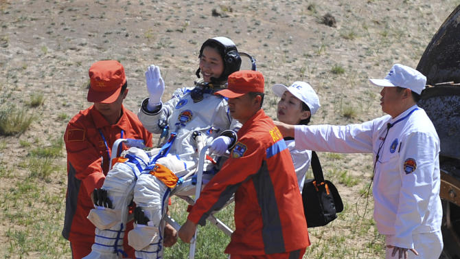 In this photo released by China's Xinhua news agency, China's first female astronaut Liu Yang waves as she is carried after coming out of the re-entry capsule, right, of Shenzhou-9 spacecraft in Siziwang Banner of north China's Inner Mongolia Autonomous Region Friday, June 29, 2012. Liu and two other crew members emerged smiling from the capsule that returned safely to earth Friday from a 13-day mission to an orbiting module that is a prototype for a future space station. (AP Photo/Xinhua, Ren Junchuan) NO SALES