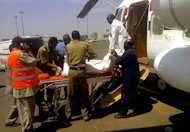Sudanese rescue workers and military personnel transport the wrapped body of a victim who was killed in a plane crash. Fifteen Sudanese military personnel were killed and seven others injured when their transport plane crashed west of Khartoum on Sunday on its way to Darfur, state media reported