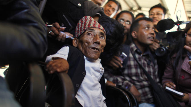 Nepalese Chandra Bahadur Dangi, 72, who says he's only 22 inches (56 centimeters) tall interacts with the media at the airport in Katmandu, Nepal, Wednesday, Feb. 22, 2012. Guinness World Records officials will be in Nepal this weekend to measure Dangi who hopes to be named the world's shortest man. Dangi is hoping to snatch the title of the world's shortest man from Junrey Balawing of the Philippines, who is 23.5 inches (60 centimeters) tall. (AP Photo/Niranjan Shrestha)