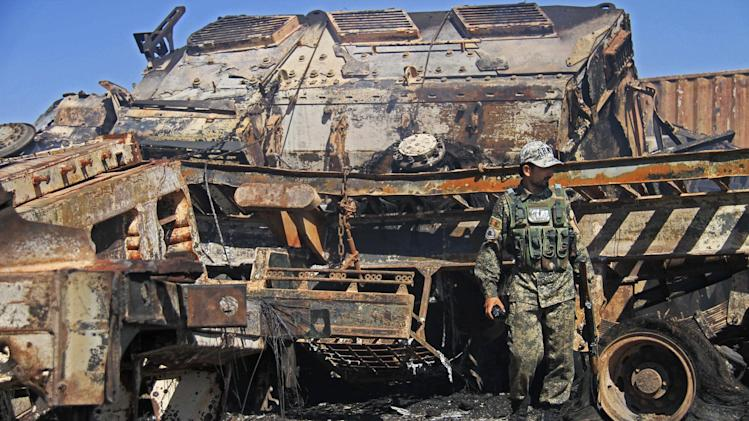 An Afghan policeman stands near a destroyed NATO supply truck