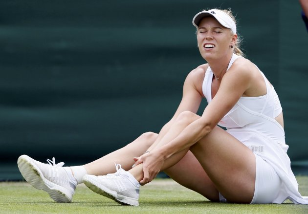 Caroline Wozniacki of Denmark holds her ankle after falling in her women's singles tennis match against Petra Cetkovska of the Czech Republic at the Wimbledon Tennis Championships, in London