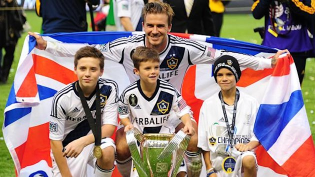 Picture taken on December 1, 2012 of David Beckham posing with his sons Brooklyn (L), Cruz (C) and Romeo and the MLS Trophy (AFP)