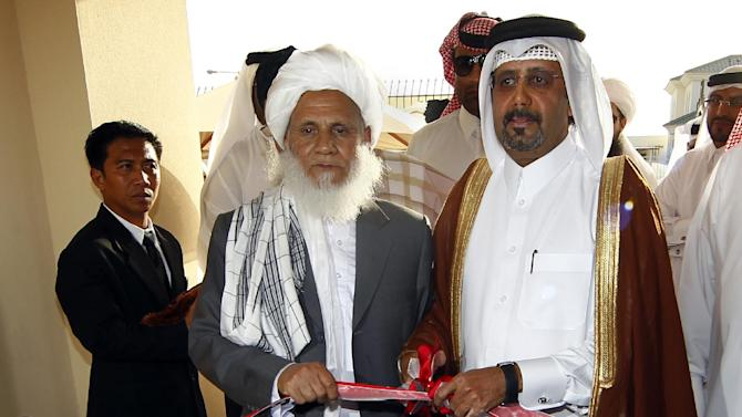 Qatari Assistant Minister for Foreign Affairs Ali bin Fahd al-Hajri, center right, and Jan Mohammad Madani, center left, one of the Taliban officials cut the ribbon at the official opening ceremony of a Taliban office in Doha, Qatar, Tuesday, June 18, 2013. In a major breakthrough, the Taliban and the U.S. announced Tuesday that they will hold talks on finding a political solution to ending nearly 12 years of war in Afghanistan as the Islamic militant movement opened an office in Qatar. American officials with the Obama administration said the office in the Qatari capital of Doha was the first step toward the ultimate U.S.-Afghan goal of a full Taliban renouncement of links with al-Qaida. (AP Photo/Osama Faisal)
