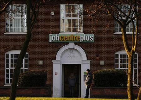 A man stands outside a state Job Centre employment office in Coalville, central England
