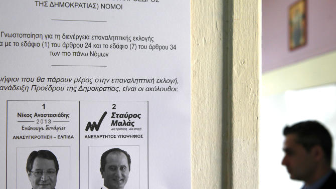 A replica of a ballot with two presidential candidates, right-wing opposition leader Nicos Anasatsiades, left, and left-wng Stavros Mallas is posted on a wall by a police officer, right, at a polling station in southern port city of Limassol, Cyprus, Sunday, Feb. 24, 2013. Opposition party leader Nicos Anastasiades garnered 45.46 per cent of the vote in the first round of voting, some 18 points over communist-backed Stavros Malas. (AP Photo/Petros Karadjias)