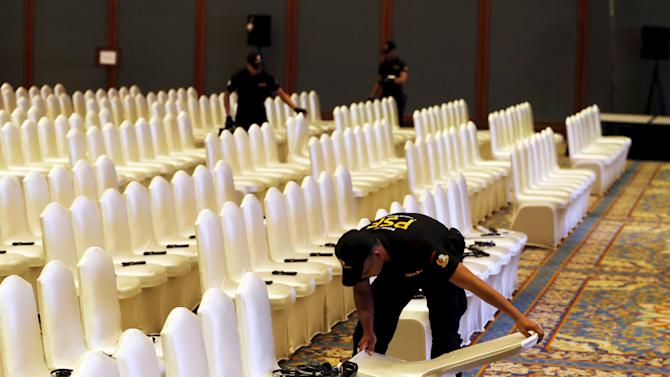 Members of the Presidential Security Forces check delegates' chairs at the venue of the Asian African Business Summit, as a side line meeting for the Asian-African Conference, in Jakarta