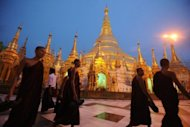 <p>Buddhist monks walk around the Shwedagon Pagoda in Yangon in June. Myanmar's parliament is considering a new investment law and a series of other measures aimed at liberalizing the economy, which was left in tatters by decades of mismanagement, cronyism and isolation under the junta.</p>