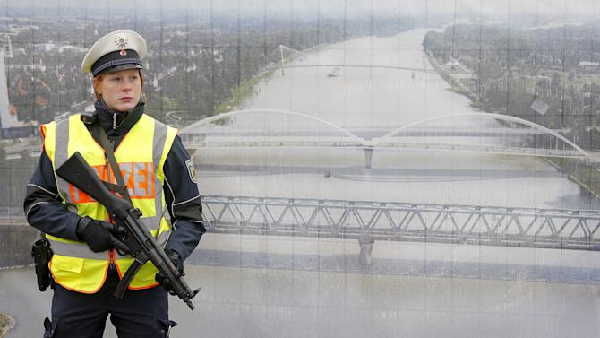 A German police officer stands in front of a poster with a picture of the Rhein river as she takes part in a control at the French-German border in Strasbourg