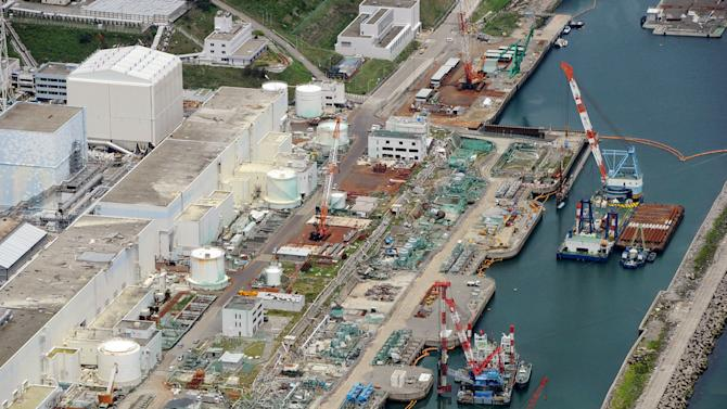 """This aerial photo taken on July 9, 2013 shows reactor buildings Unit 2, left, and Unit 1 at Fukushima Dai-ichi nuclear power plant in Okuama, Fukushima Prefecture, northern Japan. Japan's nuclear regulator says radioactive water from the crippled Fukushima power plant is probably leaking into the Pacific Ocean, a problem long suspected by experts but denied by the plant's operator. Officials from the Nuclear Regulation Authority said a leak is """"strongly suspected"""" and urged plant operator Tokyo Electric Power Co. to determine where the water may be leaking from and assess the environmental and other risks, including the impact on the food chain. The watchdog said Wednesday, July 10, 2013 it would form a panel of experts to look into ways to contain the problem. (AP Photo/Kyodo News) JAPAN OUT, MANDATORY CREDIT"""