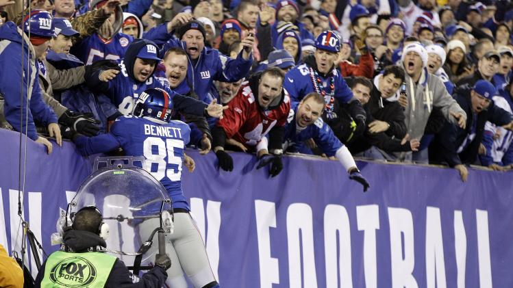 New York Giants tight end Martellus Bennett celebrates his 6-yard touchdown reception with fans during the first half of an NFL football game against the New Orleans Saints, Sunday, Dec. 9, 2012, in East Rutherford, N.J. (AP Photo/Kathy Willens)