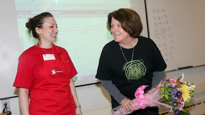 Rosemary Heffernan, a 7th grade math teacher at the Lincoln Brooks School in Lincoln, Massachusetts, accepts flowers and an apple pie in honor of Pi Day (March 14, or 3.14) courtesy of Raytheon Company.  Recognition of Pi Day is a  part of the company's MathMovesU® initiative that encourages kids to pursue careers in the science, technology, engineering and math fields.  (Aynsley Floyd/AP Images for Raytheon Company)