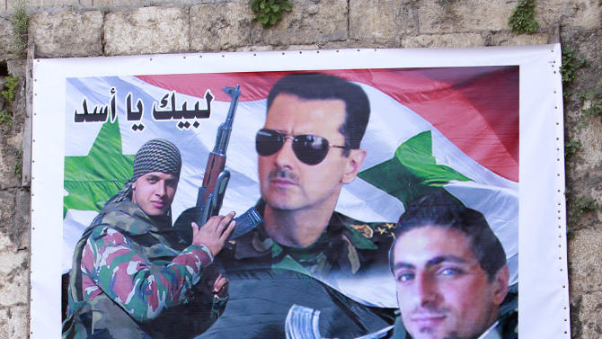 """In this Tuesday, April. 30, 2013 photo, a Lebanese man passes in front of a large poster of Syrian President Bashar Assad, center, and two Alawite fighters killed in Syria with Arabic writing that reads, """"at your service, oh Assad,"""" and, """"bullets will not terrify us and we are not scared of traitors,"""" in the predominantly Alawite neighborhood of Jabal Mohsen in the northern port city of Tripoli, Lebanon.  Lebanese members of the Syrian leader's Alawite sect fear their tiny community will be a casualty of the civil war raging in the neighboring country. Already, Sunni extremists have stoned a school bus, vandalized stores and beaten or stabbed a number of men in a wave of attacks against Lebanese Alawites, raising fears of more violence should Assad be removed from power. (AP Photo/Bilal Hussein)"""