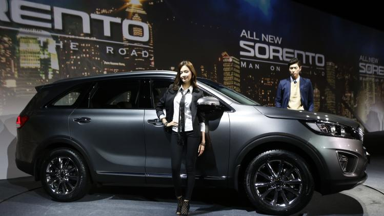 Models pose for photographs next to Kia Motors' new Sorento SUV during its launch event in Seoul