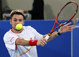 Wawrinka of Switzerland hits a return to Ferrer of Spain during Mubadala World Tennis Championship in Abu Dhabi