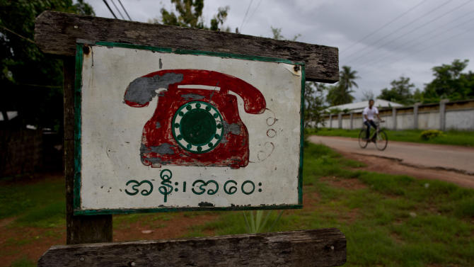 """In this June 14, 2013 photo, a roadside sign advertises a phone call facility in Hmawbi, on the outskirts of Yangon, Myanmar. Foreign companies will tap into one of the world's final telecom frontiers Thursday, June 27, 2013, when Myanmar hands out licenses to operate two new mobile phone networks — part of efforts by the long-isolated nation to use technology to spur economic development. The sign reads """"domestic and local"""" indicating phone calls can be made within Hmawbi and beyond. (AP Photo/Gemunu Amarasinghe)"""