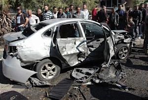 People gather around the wreckage of a car after a car bomb exploded in Homs