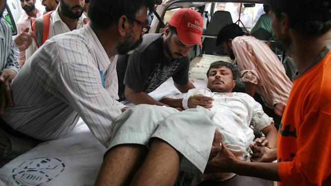 People carry a person injured in a bomb blast to a local hospital in Karachi, Pakistan on Wednesday, July 11, 2012. A bomb planted on a cycle and detonated using remote control targeted a bus carrying government employees of Pakistan Space and Upper Atmosphere Research Commission, police said. (AP Photo/Fareed Khan)