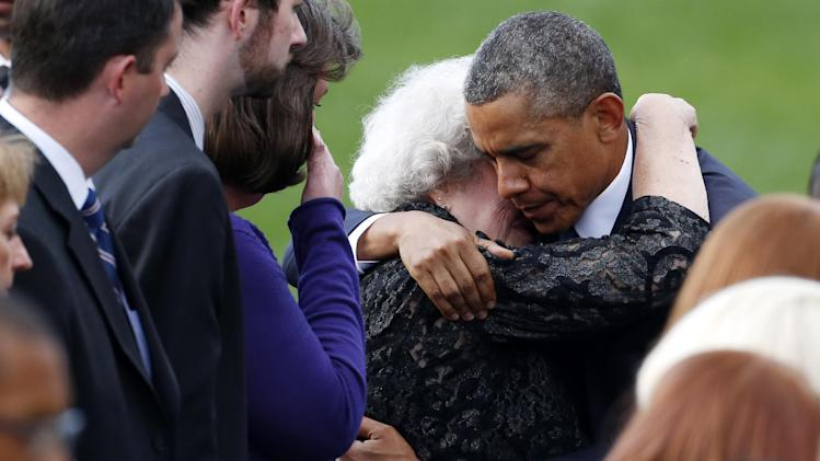 President Barack Obama comforts an unidentifed woman sitting in the family section at a memorial service for the victims of the Washington Navy Yard shooting at Marine Barracks Washington Sunday, Sept. 22, 2013. A gunman killed 12 people in the Navy Yard on Monday, Sept. 16, 2013, before being fatally shot in a gun battle with law enforcement. The president and first lady Michelle Obama also visited with the victims' families. (AP Photo/Charles Dharapak)