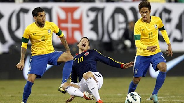 Brazil&#39;s Daniel Alves (L) tackles Colombia&#39;s James Rodriguez (C) as Brazil&#39;s Neymar looks on (Reuters)