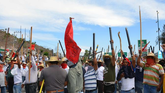 Teachers chant slogans holding up metal pipes and wooden sticks while blocking a major highway in Chilpancingo, Mexico, Thursday, April 11, 2013. The teachers, who are protesting an educational reform that will submit them to evaluation and loosen union control over hiring and firing, left peacefully after negotiating with police. (AP Photo/Alejandrino Gonzalez)