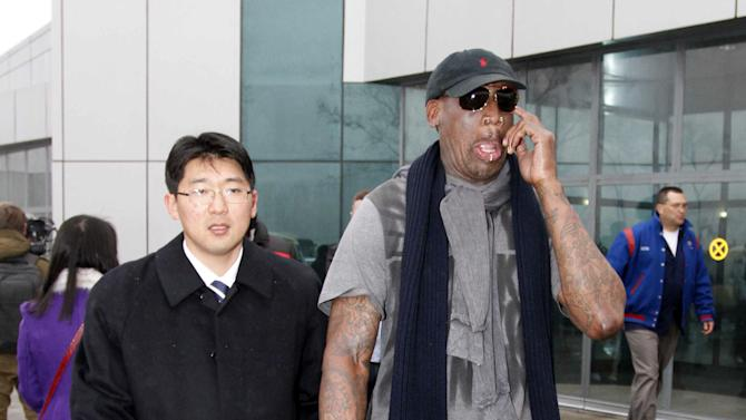 """Flamboyant former NBA star Dennis Rodman, right, scratches his face upon arrival at Pyongyang Airport, North Korea, Tuesday, Feb. 26, 2013. The American known as """"The Worm"""" arrived in Pyongyang, becoming an unlikely ambassador for sports diplomacy at a time of heightened tensions between the U.S. and North Korea. (AP Photo/Kim Kwang Hyon)"""