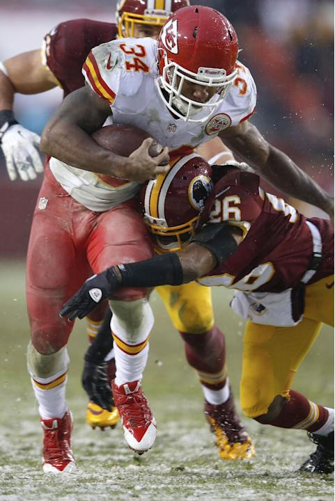 Kansas City Chiefs running back Knile Davis breaks free from Washington Redskins cornerback Josh Wilson for a touchdown during the second of an NFL football game in Landover, Md., Sunday, Dec. 8, 2013