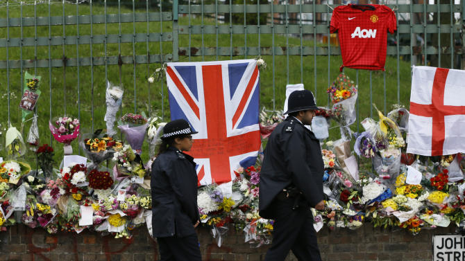 British police officers walk past some of the thousands of tributes left in honour of murdered 25-year-old British soldier Lee Rigby, near Woolwich Barracks in London, Wednesday, May 29, 2013. An autopsy shows that an off-duty soldier killed in a suspected Islamic extremist in London attack last week died from multiple cuts and stab wounds after he was hit by a car, police said Wednesday. (AP Photo/Lefteris Pitarakis)