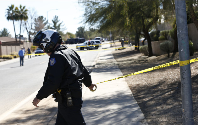 A Phoenix Police Department officer, puts up police tape near a home of a suspected gunman who opened fire at a Phoenix office building on, wounding three people, one of them critically, and setting o