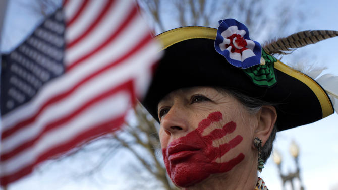 Susan Clark of Santa Monica, Calif., who opposes health care reform, stands with a red hand painted over her mouth to represent what she said is socialism taking away her choices and rights, in front of the Supreme Court in Washington, Wednesday, March 28, 2012, on the final day of arguments regarding the health care law signed by President Barack Obama. (AP Photo/Charles Dharapak)