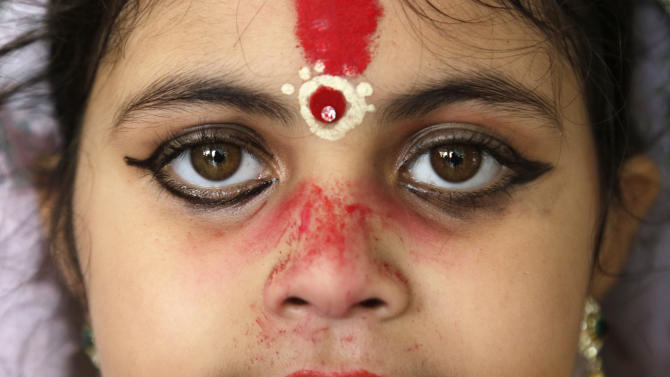 "A young Hindu girl, her face decorated with vermilion powder, sits for a ceremony where she and other girls are worshipped as ""Kumari,"" or living goddess, during Ram Navami festival, at a temple in Kolkata, India, Saturday, March 28, 2015. Ram Navami marks the birth of Hindu God Rama. (AP Photo/Bikas Das)"