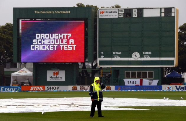 A security guard stands in the rain next to the pitch during a rain delay on the final day of the second test between England and New Zealand at the Basin Reserve in Wellington