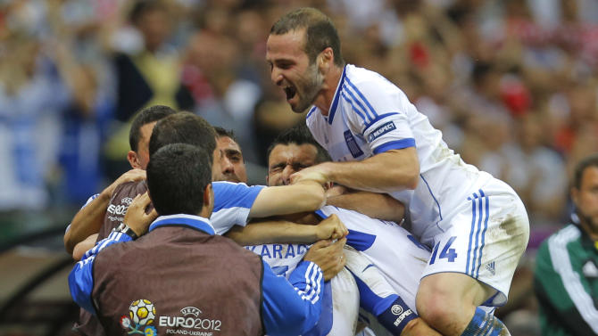 Greece's players celebrates after scoring their side's first goal  during the Euro 2012 soccer championship Group A  match between Greece and Russia in Warsaw, Poland, Saturday, June 16, 2012. (AP Photo/Sergey Ponomarev)