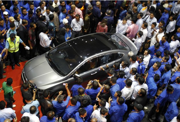 People crowd around the newly unveiled Proton Preve during its launch in Kuala Lumpur