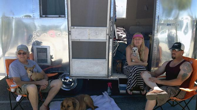 From left to right Tom Reeves, Sondra Reader and Scott Reader and their dogs rest by their trailer at a Red Cross shelter in Palmdale, Calif., on Monday, June 3, 2013, after they evacuated their home at Lake Hughes on Saturday June 1, 2013. Reader, 44, said he was astounded to see how fast-flying embers blew from a ridge a half-mile away and across Lake Hughes to suddenly ignite brush near his backyard. (AP Photo/Robert Jablon)