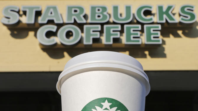 In this Thursday, July 12, 2012, photo, a cup of Starbucks coffee sits outside a shop in Cambridge, Mass. Starbucks Corp. reports quarterly financial results after the market closes on Thursday, July 26, 2012. (AP Photo/Charles Krupa)