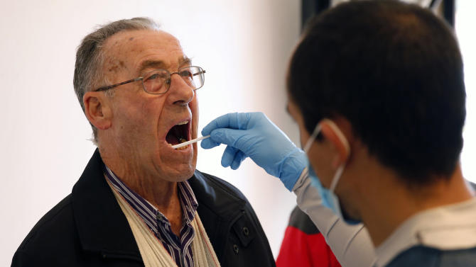 Gonzalo Carnim, forensic of the Association for the Recovery of Historical Memory, takes a saliva sample from a man for a DNA test in Guadalajara's cemetery