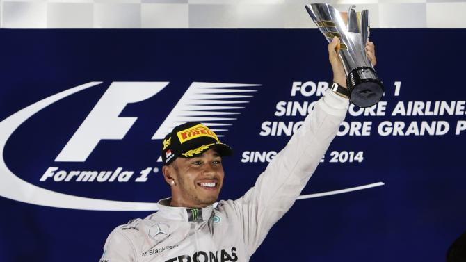 Mercedes Formula One driver Lewis Hamilton of Britain celebrates with his trophy after winning the Singapore F1 Grand Prix